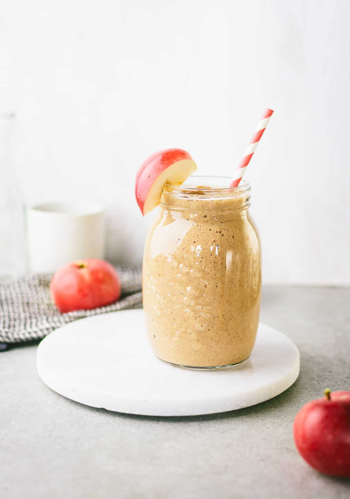 Apple pie smoothie in a glass jar, apple slice and a red stipe straw.